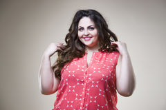 Happy plus size fashion model in casual clothes, fat woman on beige background, overweight female body Stock Photo