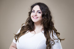Happy plus size fashion model in casual clothes, fat woman on beige background, overweight female body. Happy plus size fashion model in casual clothes, fat Royalty Free Stock Images