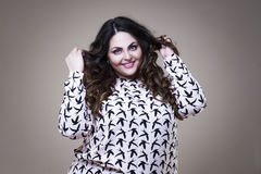 Happy plus size fashion model, fat woman on beige background, overweight female body Royalty Free Stock Photo