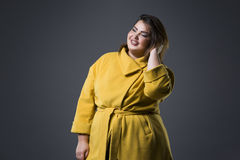 Happy plus size fashion model in yellow coat and black hat, fat woman on gray background, overweight female body Royalty Free Stock Photo