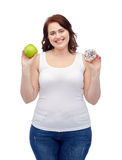 Happy plus size woman choosing apple or cookie Royalty Free Stock Images