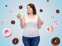 Happy plus size woman choosing apple or cookie Royalty Free Stock Photos