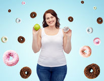 Happy plus size woman choosing apple or cookie Royalty Free Stock Image
