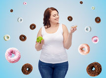 Happy plus size woman choosing apple or cookie Stock Photos