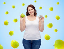 Happy plus size woman choosing apple or donut Royalty Free Stock Image