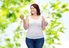 Happy plus size woman choosing apple or donut Royalty Free Stock Photo