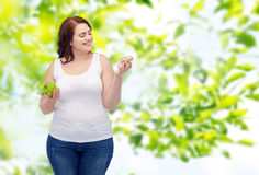 Happy plus size woman choosing apple or donut Stock Images
