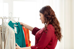 Happy plus size woman choosing clothes at wardrobe. Clothing, fashion, style and people concept - happy plus size woman choosing clothes at home wardrobe Royalty Free Stock Photography