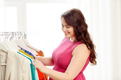 Happy plus size woman choosing clothes at wardrobe Royalty Free Stock Images