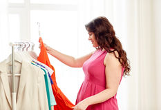 Happy plus size woman choosing clothes at wardrobe Stock Photography