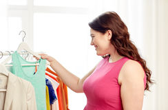 Happy plus size woman choosing clothes at wardrobe Stock Images