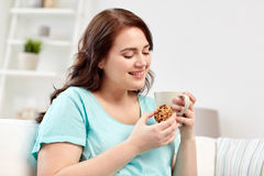 Happy plus size woman with cup and cookie at home Stock Images