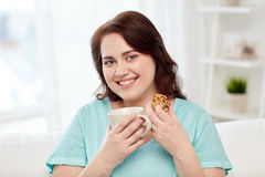 Happy plus size woman with cup and cookie at home Stock Image