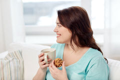 Happy plus size woman with cup and cookie at home Royalty Free Stock Photo