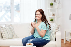 Happy plus size woman with cup and cookies at home Stock Photos