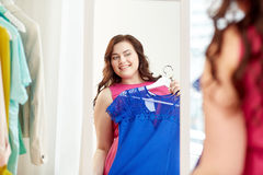 Happy plus size woman with dress at mirror Royalty Free Stock Photo