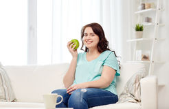 Happy plus size woman eating green apple at home Royalty Free Stock Photography