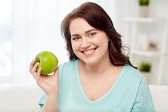 Happy plus size woman eating green apple at home Stock Image