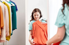 Happy plus size woman with shirt at mirror Stock Photos