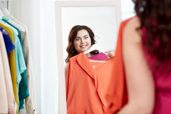 Happy plus size woman with shirt at mirror Royalty Free Stock Photography