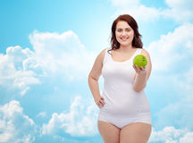 Happy plus size woman in underwear with apple Stock Image