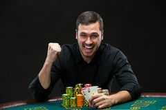 Happy poker player winning and holding a pair of aces Stock Photography