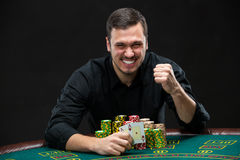 Happy poker player winning and holding a pair of aces Stock Photos