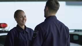 Happy police colleagues giving high-five, starting patrol shift with positive. Stock footage stock video footage
