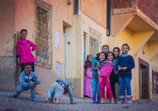 Happy poor friendly children girl and boy in Morocco village with old house. Happy, friendly girls and boys with a smile, taken in traditional Medina and country royalty free stock photo