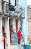 Happy but poor, people emegrge from their cramped communist styl. E home units to cool themsleves Santa Clara, Cuba, street scenes on july 1, 2012 royalty free stock photography