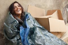 Happy poor woman. Wrapped with tarpaulin Stock Images