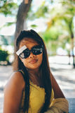 Happy portrait of Asian woman with sunglasses in summertime on the beach. Alone Stock Photo