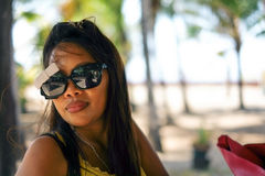 Happy portrait of Asian woman with sunglasses in summertime on the beach. Alone Royalty Free Stock Photography