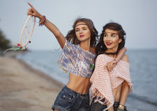 Happy portrait of two young boho woman at the sea showing at the. Happy portrait of two young boho women at the sea showing at the sky Royalty Free Stock Photography