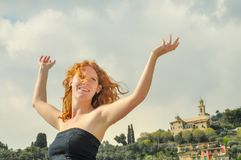 Happy happy portrait of a young elegant red-haired curly woman with arms raised at the seaside on the beach in Italy with copy stock photo