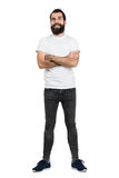 Happy positive bearded hipster in white t-shirt and tight jeans with crossed arms Stock Photography