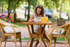 Happy, positive, beautiful, elegance  girl sitting at cafe table outdoors. Royalty Free Stock Image