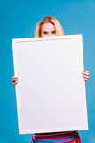 Happy positive blonde woman holding blank white board Stock Photo