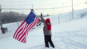 Man with US flag on a ski slope. Happy positive caucasian Man waving a flag of the United States of America winter time on a ski slope stock footage