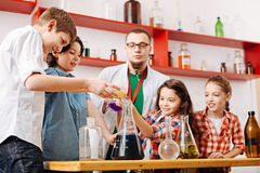 Happy positive children carrying out an experiment together. Team work. Happy positive delighted children standing around the table and carrying out a chemical Stock Photo