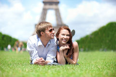 Happy positive couple laying on the grass in Paris. Closeup of happy positive couple laying on the grass in Paris near the Eiffel tower Royalty Free Stock Images