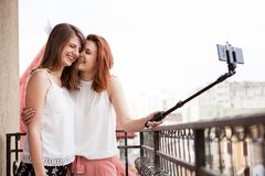Happy and positive female friends taking a selfie. At the balcony Stock Photos