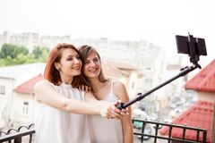 Happy and positive female friends taking a selfie. At the balcony Royalty Free Stock Photos