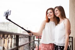 Happy and positive female friends taking a selfie. At the balcony Royalty Free Stock Image