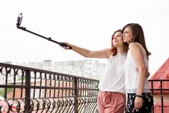Happy and positive female friends taking a selfie. At the balcony Stock Photography