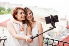 Happy and positive female friends taking a selfie. At the balcony Royalty Free Stock Photography