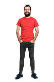 Happy positive friendly bearded man in red t-shirt and tight jeans laughing at camera. Full body length portrait isolated over white studio background stock photos