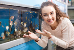 Happy positive girl looking at tropical fish Stock Photography
