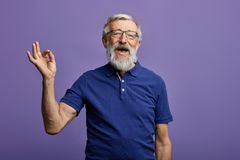 Happy positive handsome old man shows Ok sign, no problems, health is ok. stock images