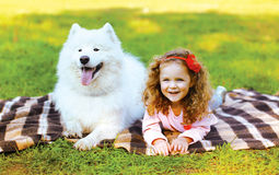 Happy positive little girl and dog having fun in sunny autumn Stock Image